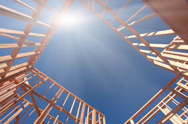 The sun shining through a building frame